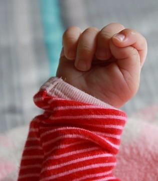 宝宝总是把拳头握得紧紧的 是怎么回事?
